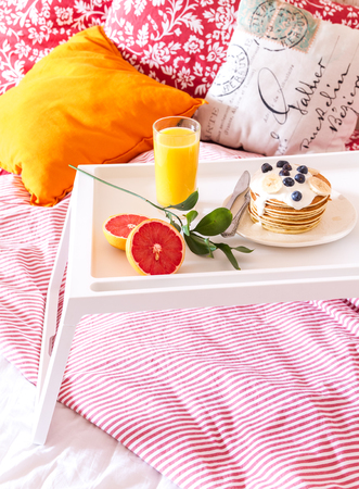 luxuries: Concept of breakfast in bed on tray with juice.