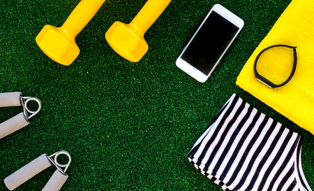 concept preparing to fitness sports equipment top view on green background mock up