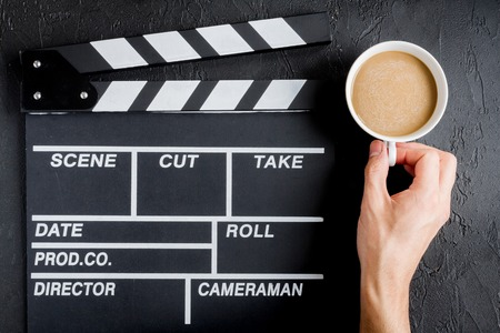 screenwriter: Screenwriter desktop with movie clapper board dark background top view