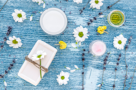 cremas faciales: organic cosmetics with camomile on blue background top view. Foto de archivo