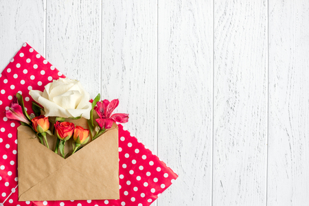 envelope and flowers on wooden background top view mock up Stock Photo