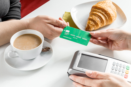 bankcard: Credit card payment bill in cafe for croissant and coffee on white table background