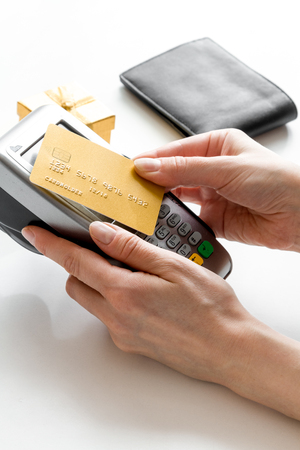 bankcard: Present purchase in shop with payment by credit card on white table background