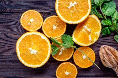 orange juice with mint squeezing on wooden kitchen background top view