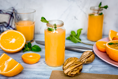 healthy orange cocktail with mint leaves in bottle on kitchen background Stock Photo