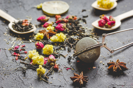 Tea herbs and spoons on grey stone background Stock Photo
