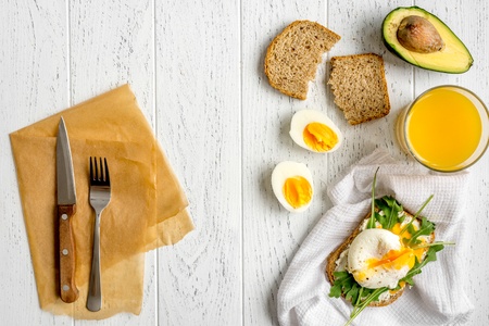poached: sandwich with poached eggs on wooden background top view.