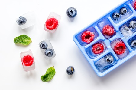 blueberry and raspberry in icetray on stone background top view Archivio Fotografico