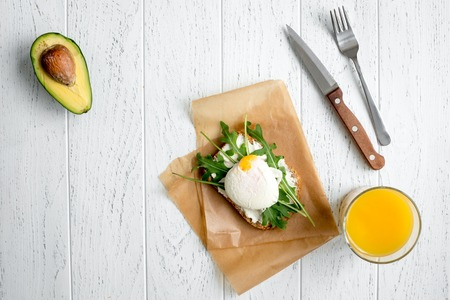 poached: sandwich with poached eggs on wooden background top view