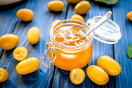 kumquat on plate and jam in jar at wooden table Archivio Fotografico
