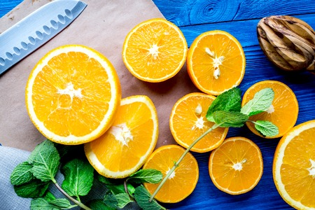 orange juice with mint squeezing on blue kitchen background top view Stock Photo