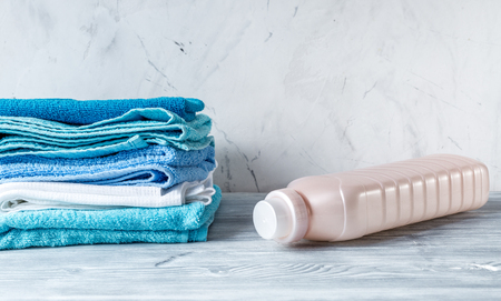 absorbent: housekeeping set with towels and plastic bottles on laundry background mock-up Stock Photo