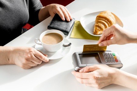 Croissant and coffee business breakfast on white table background payment by credit card in cafe