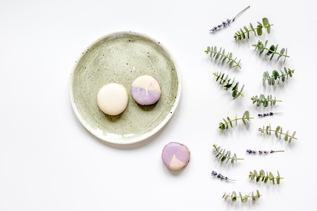 Trendy design with macaroons on plate, eucalyptus and lavander top view Stock Photo