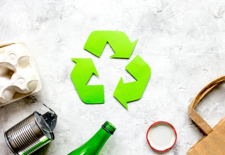 waste recycling symbol with garbage on stone background top view mockup