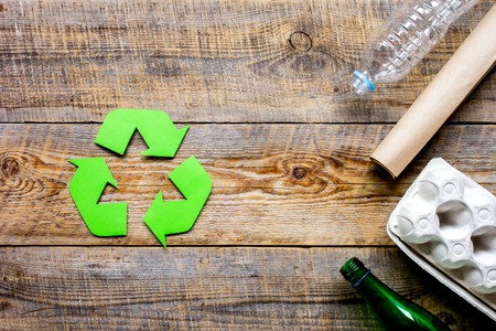 recycling symbol with waste on wooden background top view mockup