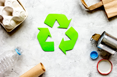 Eco concept with recycling symbol and garbage on stone table background top view Stock Photo