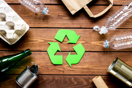 recycling symbol with waste on wooden desk background top view Stock Photo