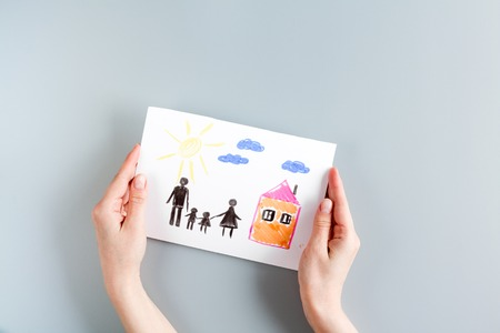top veiw: happy family concept with card and hands on gray desk background top view mock up