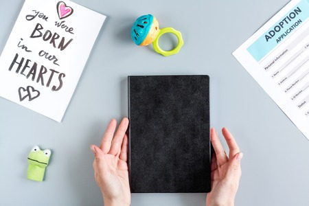 top veiw: Adoption concept with notebook and hands on gray table background top view Stock Photo
