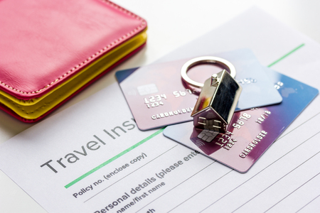 Travel insurance application form with credit cards and passport on white desk background Stock Photo