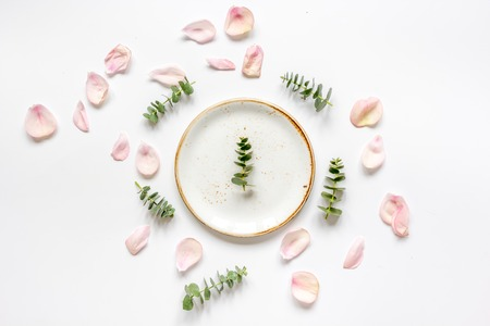 Spring trandy design with plate and blossom in soft light on white background top view mockup