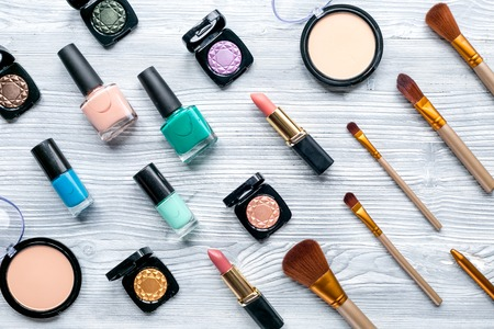 decorative cosmetic set with eye shadow and make-up brushes on light woman table background top view