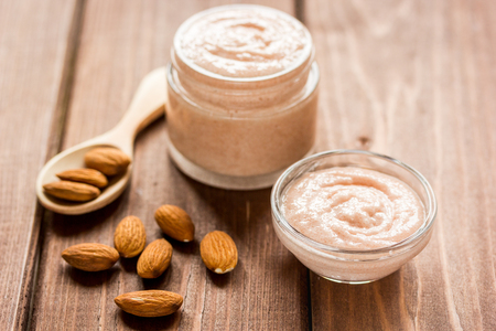 bath essence: organic body scrub with almonds for body care concept on wooden table background