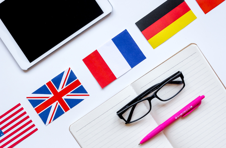 lifestyle learning english online with flags and tablet on white table background top view Stock Photo