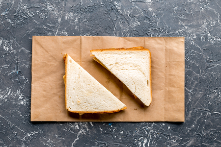 fresh sandwich and paper bag on gray table background top view mock-up