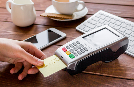 bankcard: Payment for breakfast in cafe with keyboard and telephone, credit card and terminal on wooden table background Stock Photo