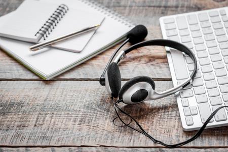 Call center manager desk con auricolare e tastiera su sfondo in legno Archivio Fotografico - 75093185
