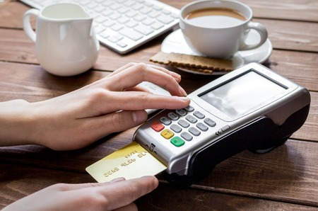 bankcard: Payment for breakfast with card and terminal on wooden table background Stock Photo