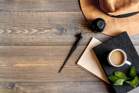 space for type: professional writer workplace with tools, cup and hat on wooden desk background top view mockup Stock Photo