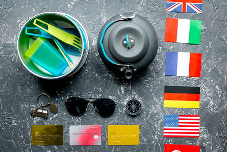 plactic: traveller lifestyle items with compass and plactic dishes on gray table background top view