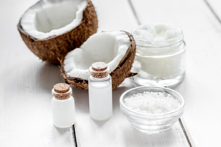 bath essence: fresh coconut with organic cosmetic oil in glass jar on white background