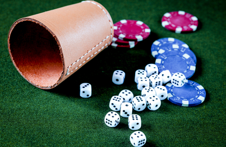 poker chips and dice on green background
