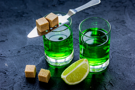 absinthe in glass with lime slices on dark background Stock Photo