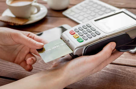 bankcard: Online payment concept with credit card and terminal for business lunch on wooden table background