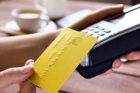 木製のテーブル背景にカフェでターミナルはクレジット カード支払いとコーヒーを購入します。