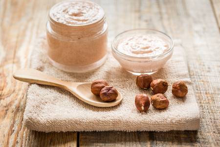 bath essence: organic cosmetic for women body care with natural huzelnut scrub on desk background