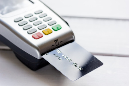 wireless terminals: payment terminal with card on table background