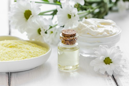 woman bath: Chamomile essential oil in glass bottle in cosmetic set on table background