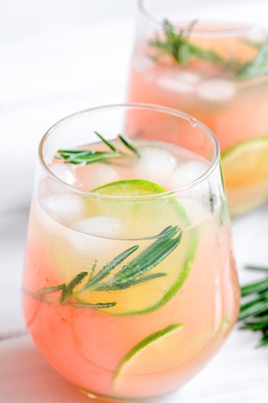 breackfast: fitness cocktail in glass with lime and rosemary on white table background