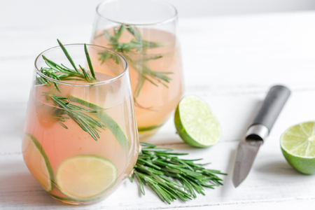 breackfast: vegetable smoothie with lime and rosemary in glass on white table background