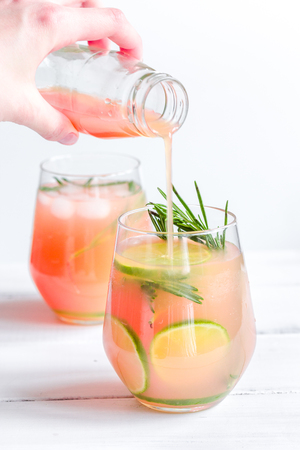 breackfast: pouring fresh juice in glass with lime and rosemary on white table background