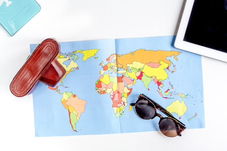stuff: tourist lifestyle with camera and map white table background top view