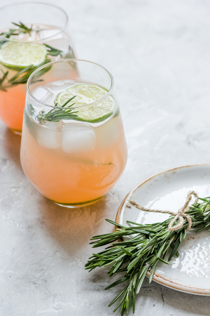 breackfast: fitness cocktail in glass with lime and rosemary on stone table background