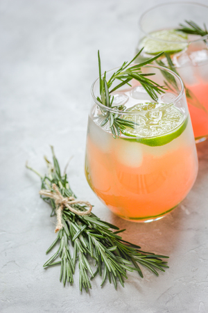 breackfast: Glass of fresh juice with lime and rosemary on stone table background