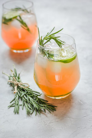 breackfast: glass of fresh juice with lime and rosemary for healthy drink on stone kitchen table background